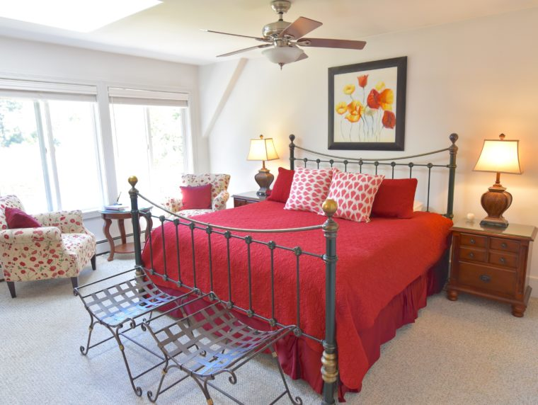 Swan Room with red bedspread on king bed and comfortable chairs for relaxing