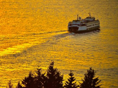 Ferry boat crossing water at sunset
